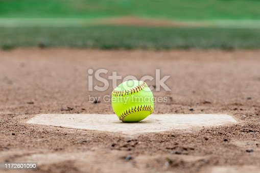 Softball laying on a worn home plate or base