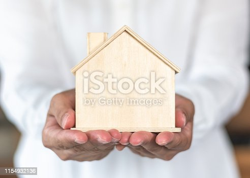 istock Home property ownership for rent, sale, leasing and safety insurance concept with new house in landloard or real estate realtor hand giving to buyer, renter or tenant 1154932136