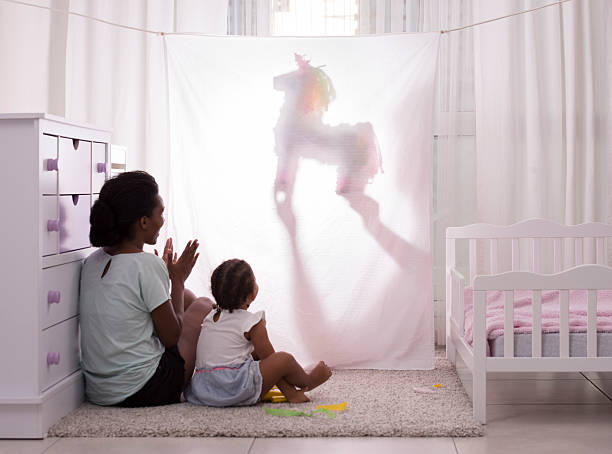 Home puppet show time. Father performing puppet shadow show to his 2.5 years old daughter and wife. Actor dimming the light with a unicorn puppet toy behind white curtain. Curious child enjoying to watch. Mother applauding. hide and seek stock pictures, royalty-free photos & images