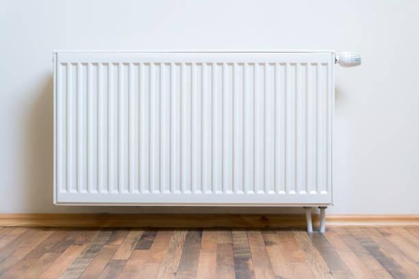 Heizkörperheizung an der weißen Wand auf Holzholzboden. Verstellbare Wärmedämmgeräte für Wohnung und Wohnung – Foto