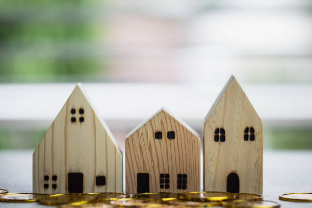 Home real estate mortgage concept : House Miniature model with stack money coins show for selling. Ideas for offers of mortgage loan investment, management agreement building to buy new residential stock photo