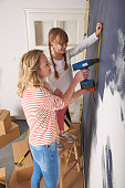 Shot of mother and her cute daughter renovating their home.