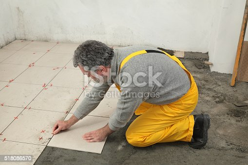 istock Home renovation, worker placing tile 518086570