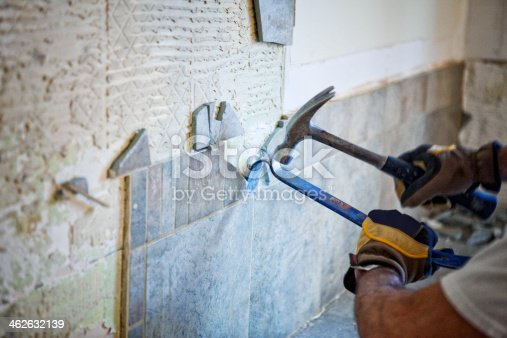 Man removing tile out old kitchen during home renovations.