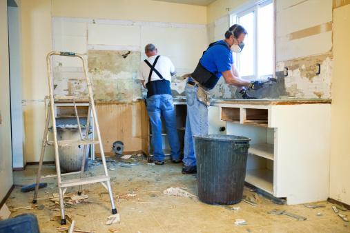 Construction worker using pneumatic hammer, construction site concept.
