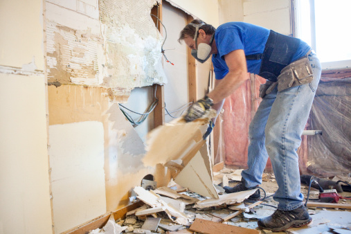 Man tearing out old kitchen during home renovations.