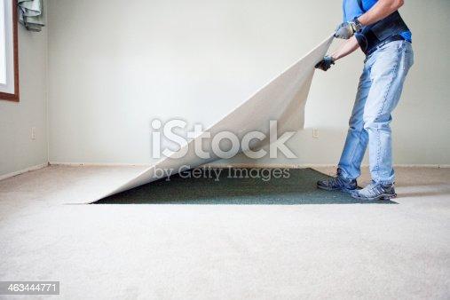 Man removing carpet during home renovations.