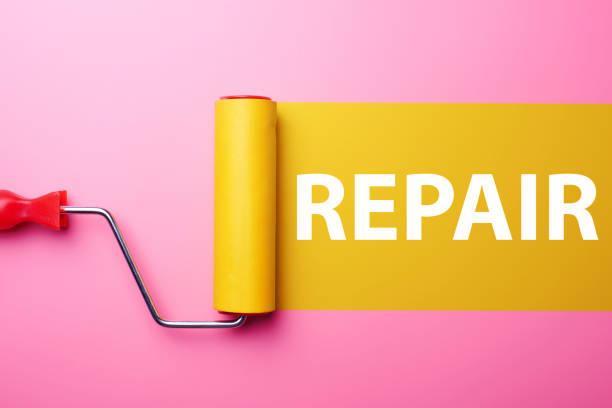 Hausreparaturkonzept. Gelbe Walze für Tapete und rosa Wand mit Kopierplatz. – Foto