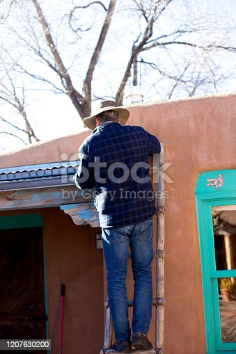 Home Repair: Man on Ladder Fixing/Cleaning Gutter