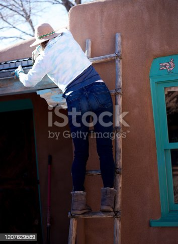 Home Repair: Woman on Ladder Fixing/Cleaning Gutter
