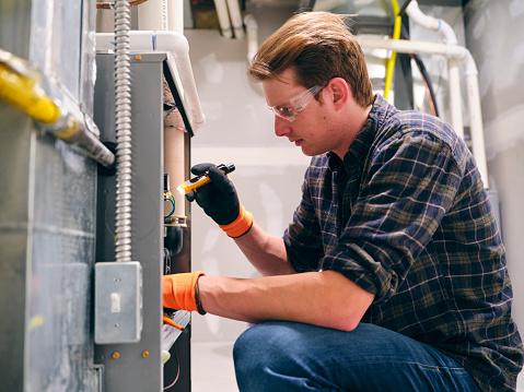 A repairman working inside a home, repairing a furnace.
