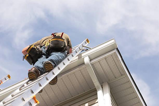 home repairs handyman up a ladder outdoors - ladder stockfoto's en -beelden