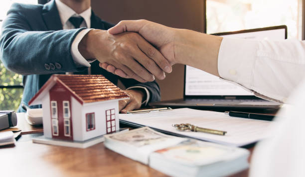 Home sales agents and buyers work on signing new homes and shaking hands. stock photo