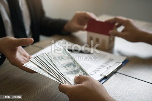 481337750istockphoto Home sales brokers and real estate investors are exchanging with investors being filing cash at the agent's hand. 1166138650