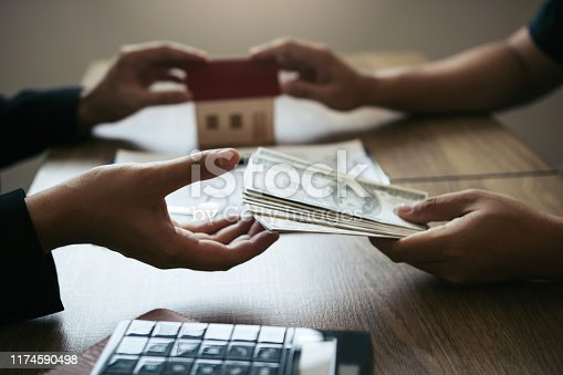 481337750istockphoto Home sales brokers and real estate investors are exchanging with investors being filing cash at the agent's hand. 1174590498