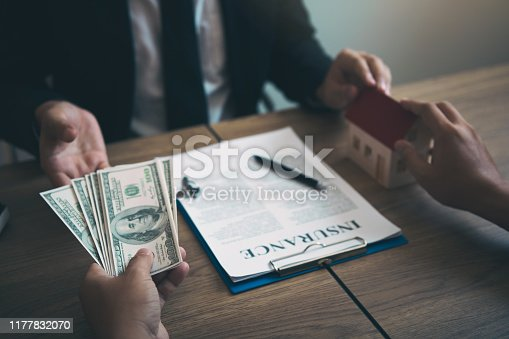 481337750istockphoto Home sales brokers and real estate investors are exchanging with investors being filing cash at the agent's hand. 1177832070