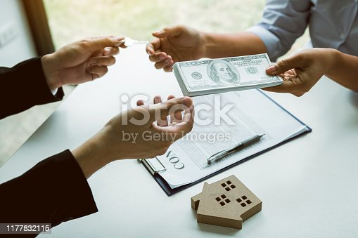 481337750istockphoto Home sales brokers and real estate investors are exchanging with investors being filing cash at the agent's hand. 1177832115