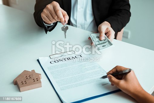 481337750istockphoto Home sales brokers and real estate investors are exchanging with investors being filing cash at the agent's hand. 1185167659