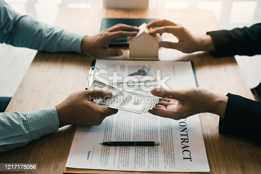 481337750 istock photo Home sales brokers and real estate investors are exchanging with investors being filing cash at the agent's hand. 1217175056