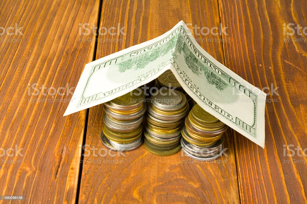 Home savings, budget concept. Model house and coins on wooden royaltyfri bildbanksbilder