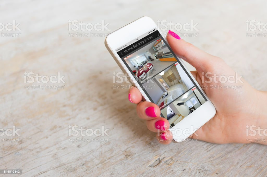 Home security cameras viewed on mobile phone stock photo
