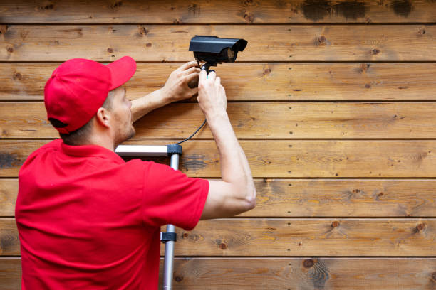 home security - man installing outdoor surveillance camera on wooden wall copy space stock photo