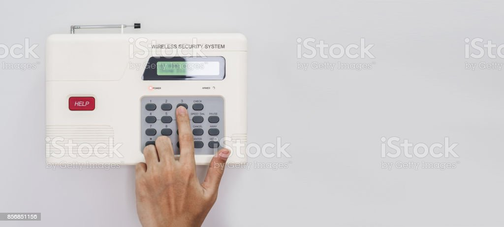 Home security system, Hand entering code on home security keypad, on white wall with copy space stock photo