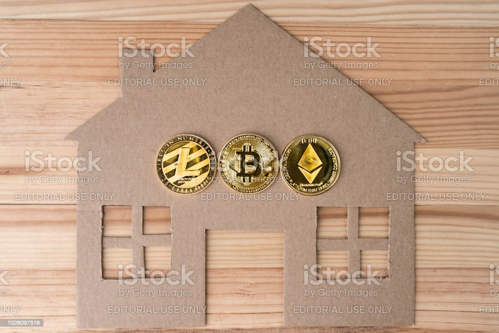 GDANSK, POLAND - August 16, 2018: Home shape with physical Bitcoin, Litecoin and Ethereum coins. stock photo