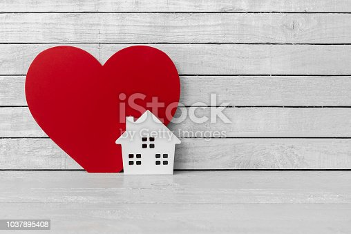 istock Home Shaped with Red Heart Shaped on white wood over white wood background 1037895408