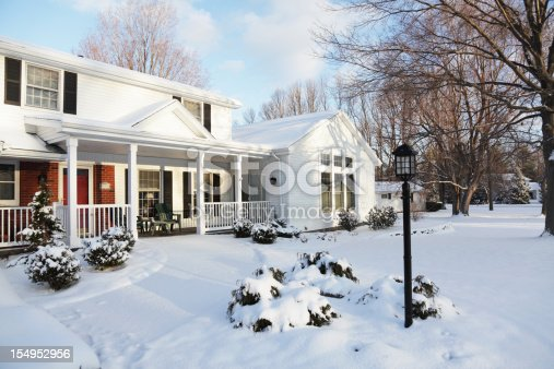 Soft early morning sunlight illuminates a newly remodeled suburban neighborhood home. Several shrubs are still buried in snow, but this very early spring snowfall will soon melt. Horizontal orientation.