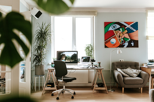 Photo series of a digital artist working at his home studio/office and doing video podcast while drawing a digital painting on a digital surface/tablet.