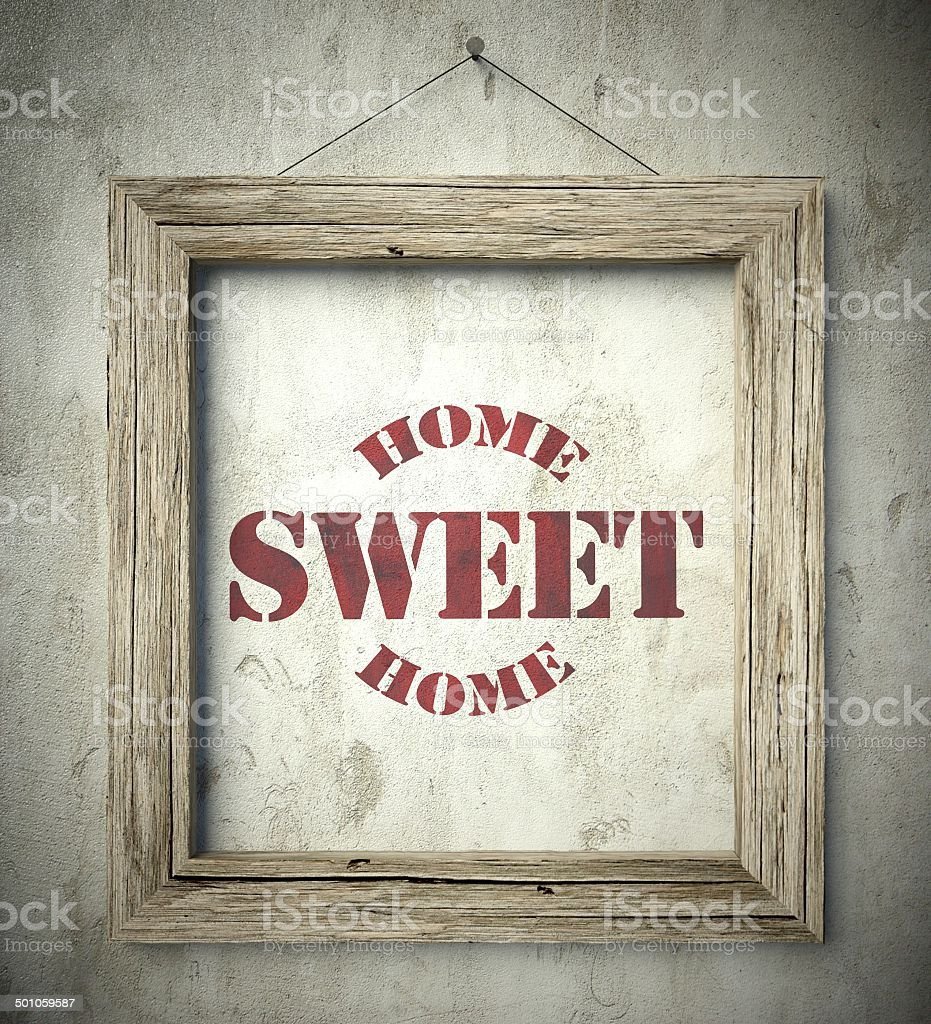 Home sweet home emblem in old wooden frame stock photo