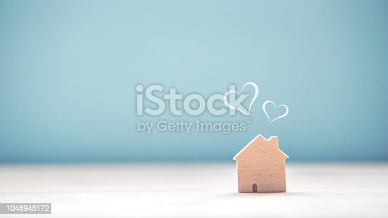 Home sweet home, house wood with heart shape on wooden and blue background