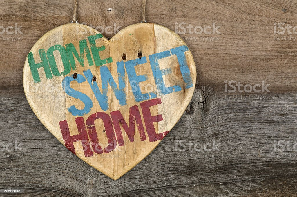 'Home Sweet Home' message wooden heart sign on rough grey stock photo