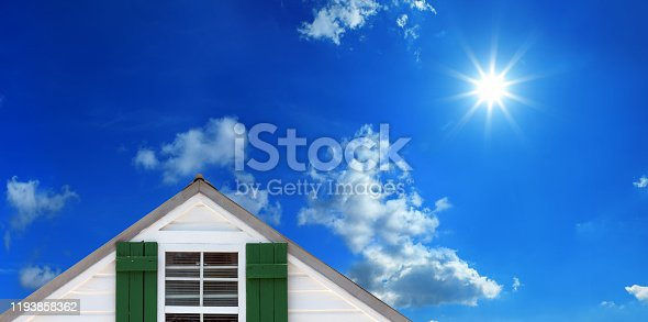 Close up house with single window over sunny blue sky with shinning sun