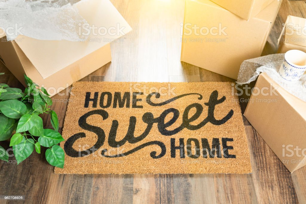 Home Sweet Home Welcome Mat and Moving Boxes on Hard Wood Floor stock photo