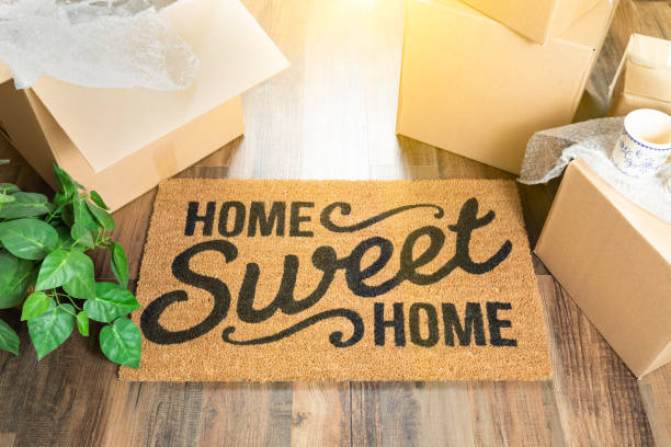 home sweet home welcome mat and moving boxes on hard wood floor - home sweet home imagens e fotografias de stock