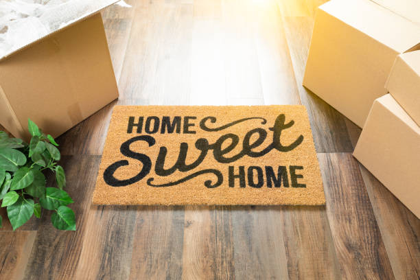 home sweet home welcome mat, moving boxes and plant on hard wood floors - home sweet home imagens e fotografias de stock