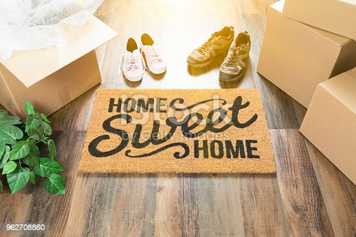 istock Home Sweet Home Welcome Mat, Moving Boxes, Women and Male Shoes and Plant on Hard Wood Floors. 962708860