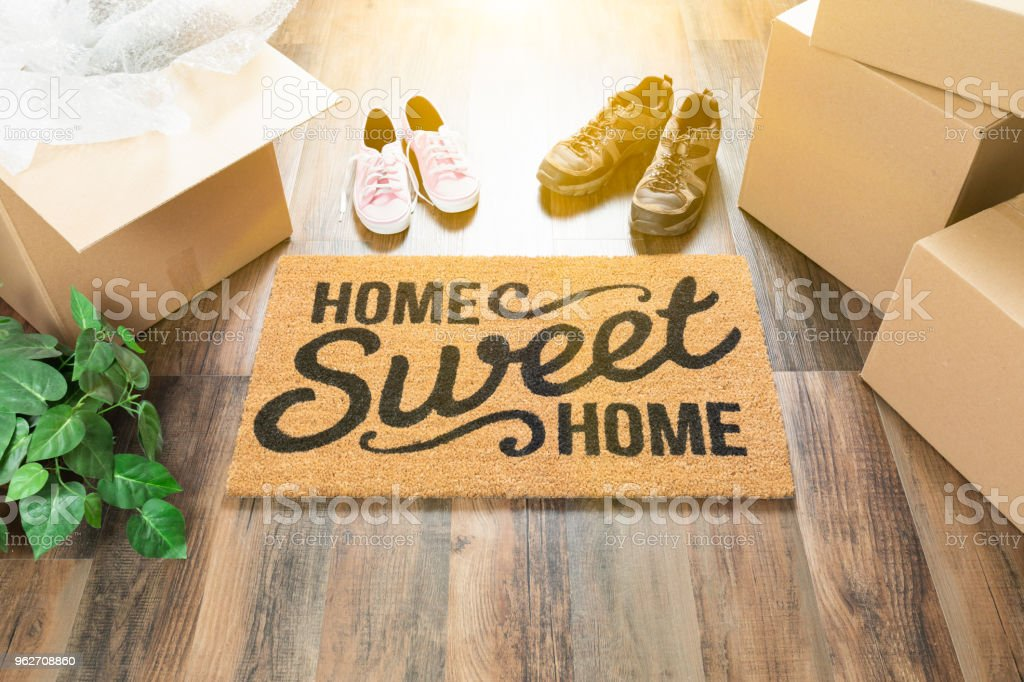 Home Sweet Home Welcome Mat, Moving Boxes, Women and Male Shoes and Plant on Hard Wood Floors. stock photo
