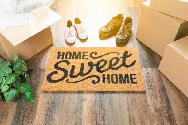 home sweet home welcome mat, moving boxes, women and male shoes and plant on hard wood floors. - house hunting stock photos and pictures