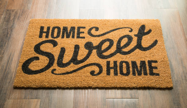 home sweet home welcome mat on floor - welcome foto e immagini stock