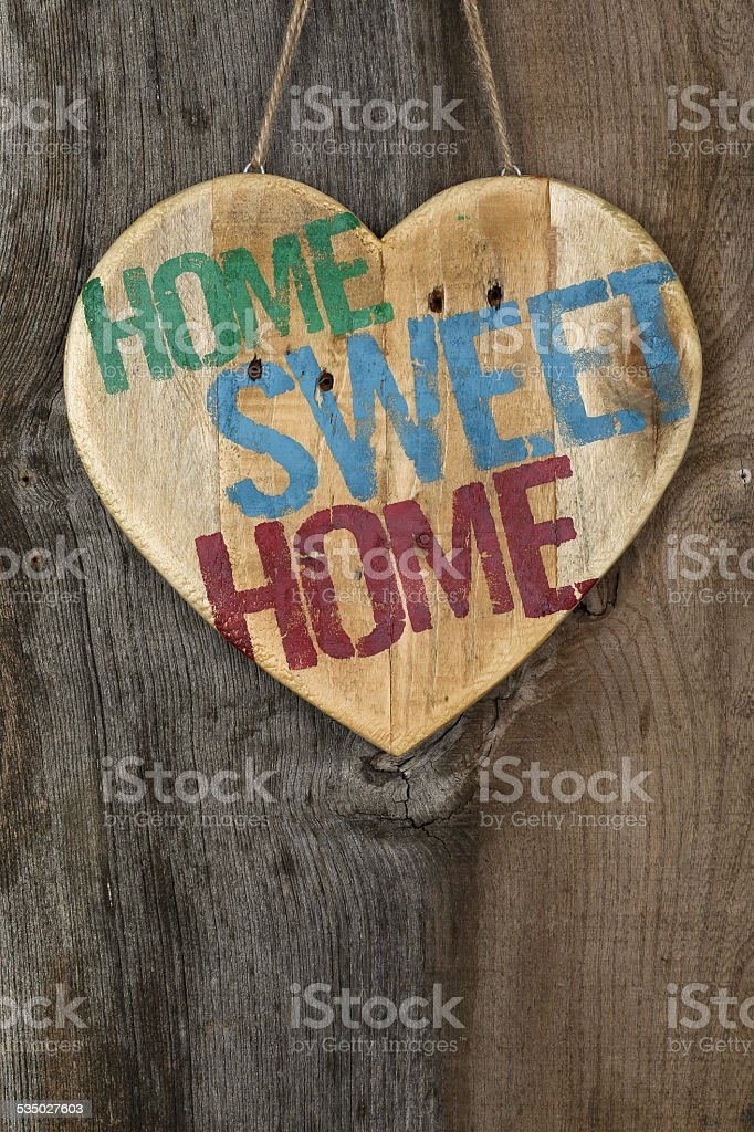 Home Sweet message wooden heart sign on rough grey wooden stock photo