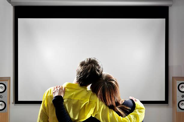 heimtheater paar, umarmen sich von filmen auf dem großen bildschirm - große leinwand stock-fotos und bilder
