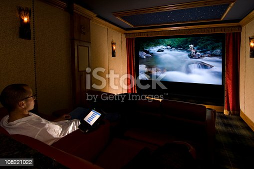 A man sits in is home theater watching a movie with copy-space.