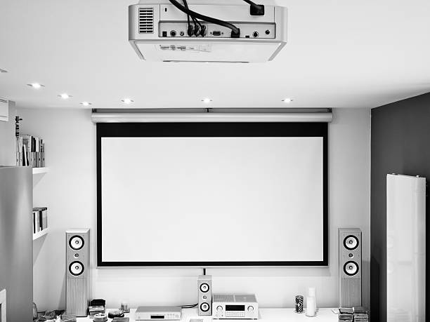home theater system, HD projector, large screen, hifi sound system Home theater system. HD projector, large 102 inches screen and hifi 6.1 sound system. Processed for black and white. overhead projector stock pictures, royalty-free photos & images