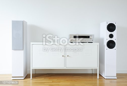 Home Theater System.Modern audio stereo system with white speakers on bureau in modern interior