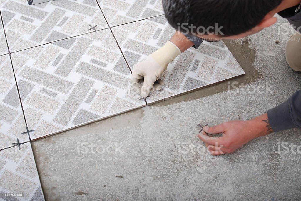 Home tile improvement - handyman with level stock photo