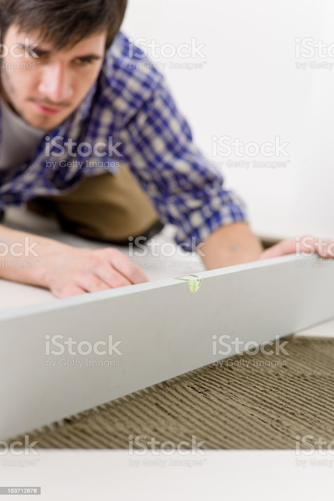 Home tile improvement - handyman with level royalty-free stock photo