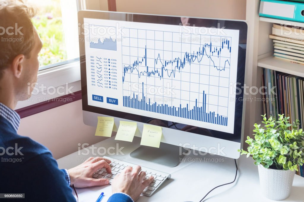 Home trader analyzing forex trading charts on computer screen investment stock photo